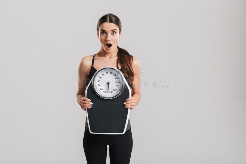 Photo of brunette athletic woman holding scale and expressing surprise on face, isolated over gray background. Photo of brunette athletic woman holding scale and stock photography