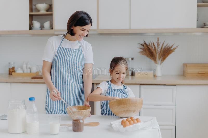 Photo of brunette mother and little kid make cookie dough, whisk ingredients in bowl, dressed in aprons, mum rejoices having small. Helper at kitchen. Cooking royalty free stock photography
