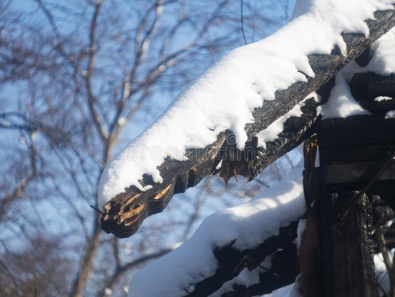Photo of a burnt house in winter. Charred beams of a wooden house. Burned down house stock images