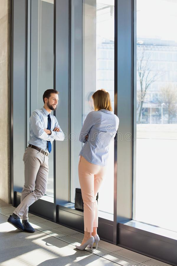 Business professionals talking while leaning on wall in office hall during break. Photo of Business professionals talking while leaning on wall in office hall royalty free stock images