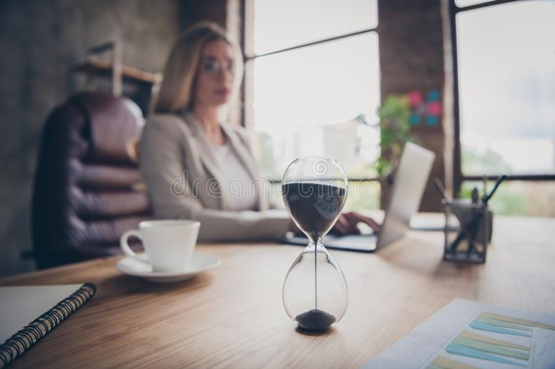 Photo of business woman looking at hourglass counting time till the end of the work day finishing her project in time stock photo