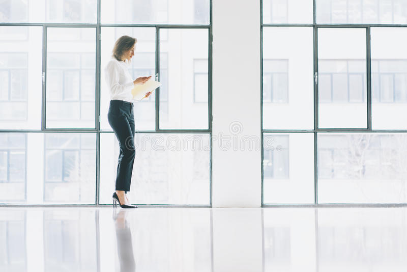 Photo business woman wearing modern suit, looking mobile phone and holding papers in hands. Open space loft office royalty free stock photos