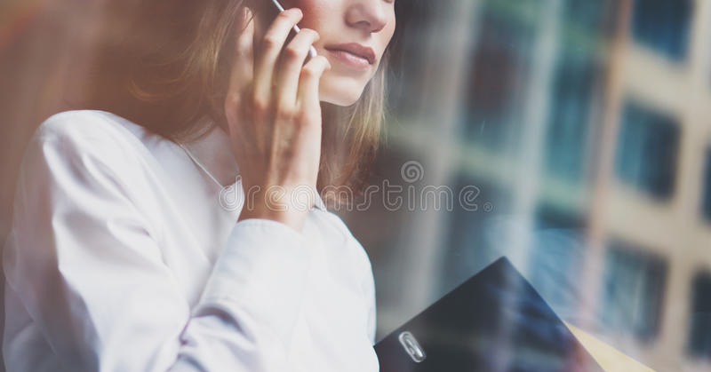 Photo business woman wearing modern suit, talking smartphone and holding documents in hands. Open space loft office royalty free stock photography