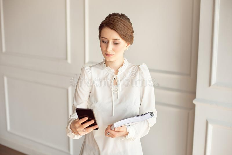 Photo business woman wearing suit, looking smartphone and holding documents in hands royalty free stock image