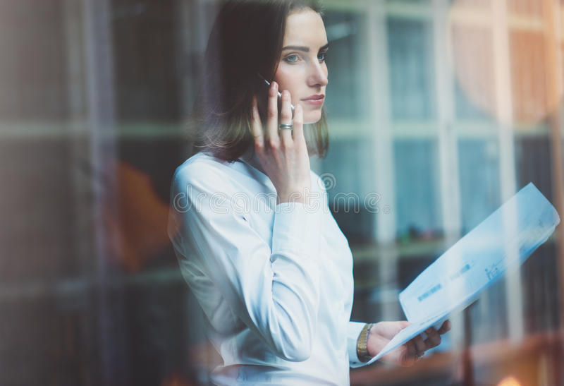 Photo business woman wearing white shirt, talking smartphone and holding documents in hands. Open space loft office. Panoramic win. Dows background stock photos