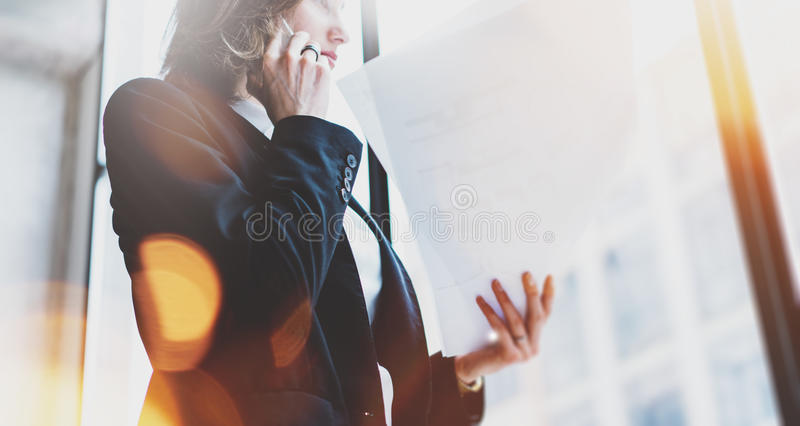 Photo business woman wearing white shirt, talking smartphone and holding documents in hands. Open space loft office. Panoramic win royalty free stock photo