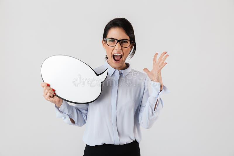 Photo of businesslike female worker wearing eyeglasses holding blank thought bubble, isolated over white background. Photo of businesslike female worker wearing stock photo