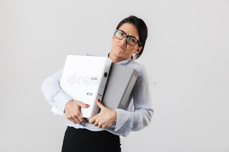 Photo of businesslike female worker wearing eyeglasses holding paper folders in the office, isolated over white background. Photo of businesslike female worker royalty free stock photo