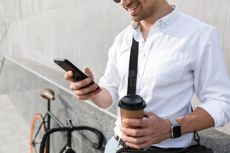 Photo of businesslike man 30s wearing sunglasses, drinking takeaway coffee and using mobile phone while standing with bicycle. Photo of businesslike man 30s royalty free stock photos