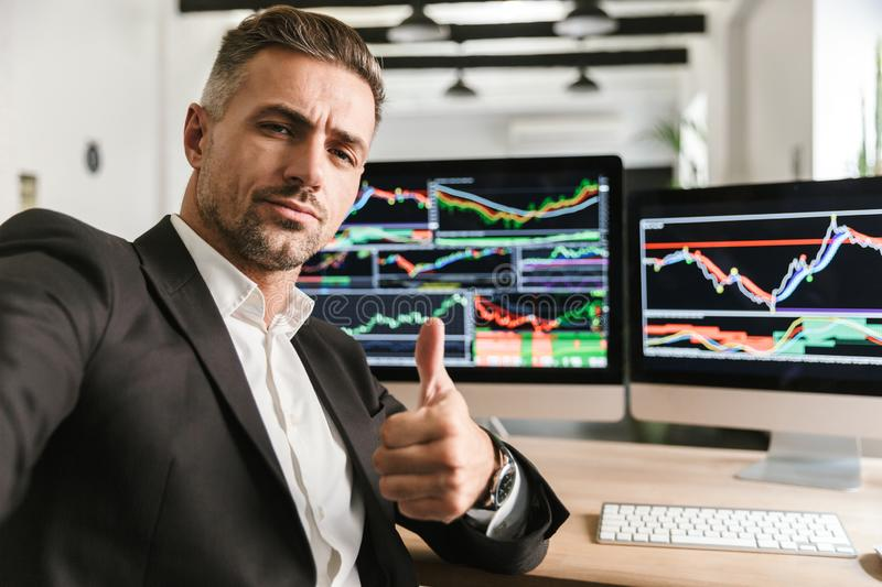 Photo of businesslike man taking selfie while working in office on computer with graphics and charts. Photo of businesslike man 30s wearing suit taking selfie stock photography