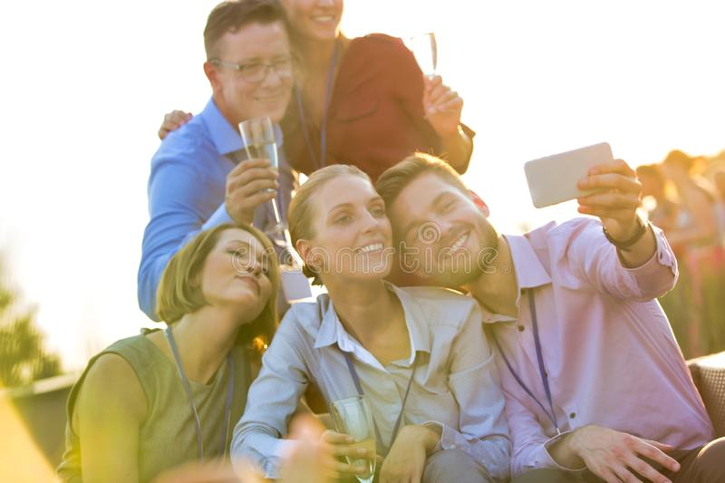 Businessman taking selfie with colleagues during rooftop party royalty free stock photography