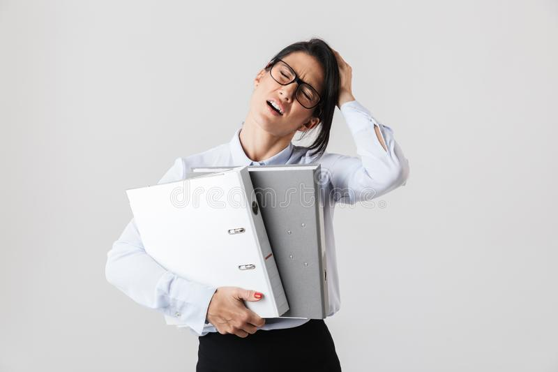 Photo of businesswoman wearing eyeglasses holding paper folders in the office, isolated over white background stock image