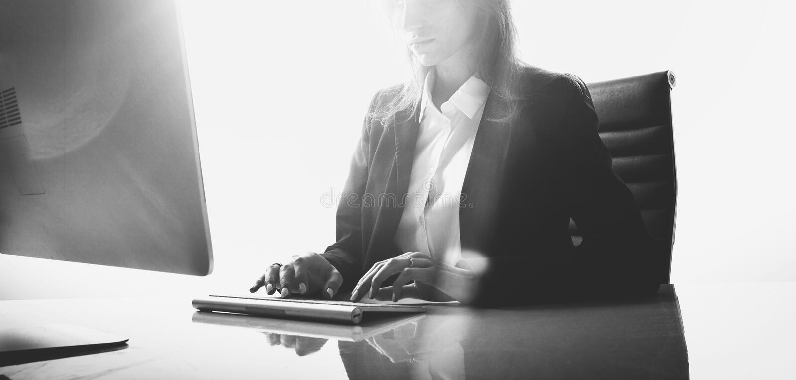 Photo of businesswoman working at table in modern, empty office. White background, wide. Black white royalty free stock image