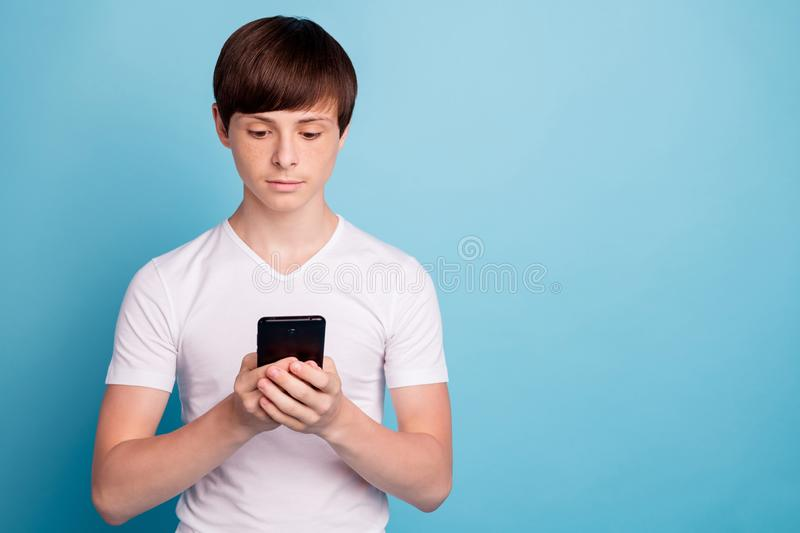 Photo of calm boyfriend browsing through his phone in search of something special while isolated with blue background stock photography