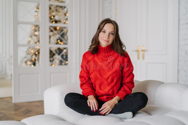 Photo of calm carefree girl wears warm doemstic clothes, poses on white couch, looks directly at camera, spends winter weekend at royalty free stock images