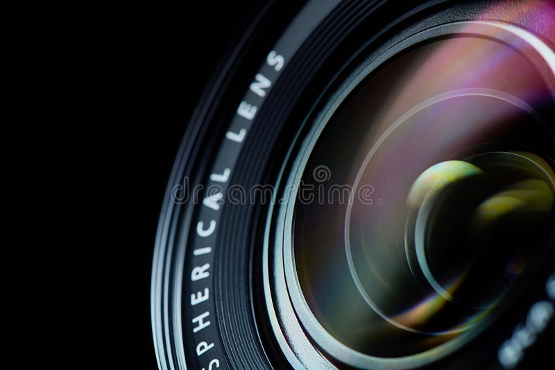 Photo camera lens closeup. Closeup of the photo camera aspherical lens on black stock photography