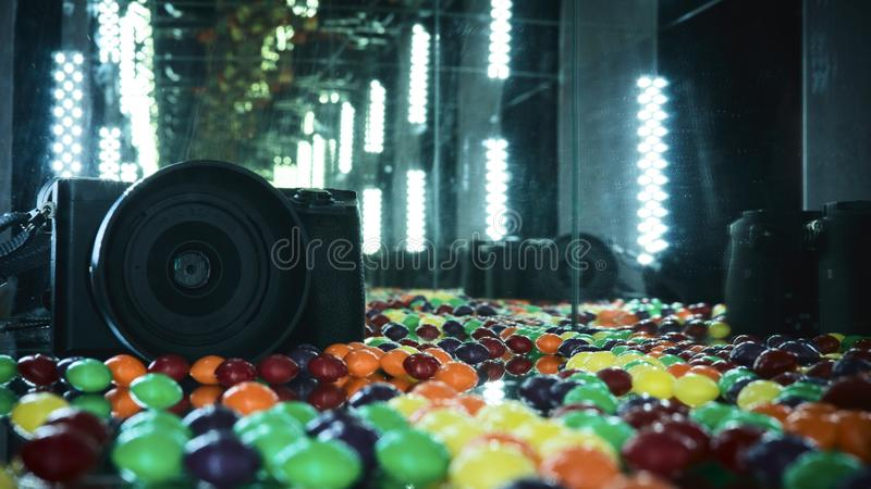 Photo camera in the mirror cube with colorful candys. Photo camera in the mirror cube with colorful stock photos