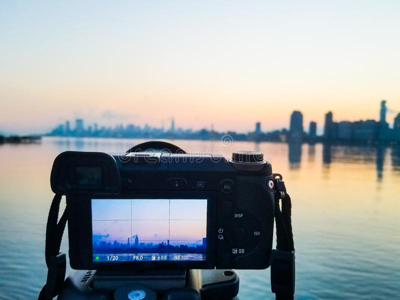 Photo camera on tripod shooting cityscape of Manhattan, NYC downtown. Early morning. View from Hudson river royalty free stock photo