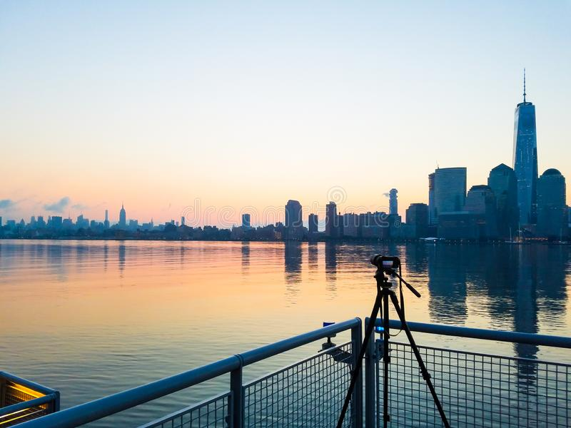 Photo camera on tripod shooting cityscape of Manhattan, NYC downtown. Early morning. View from Hudson river stock image