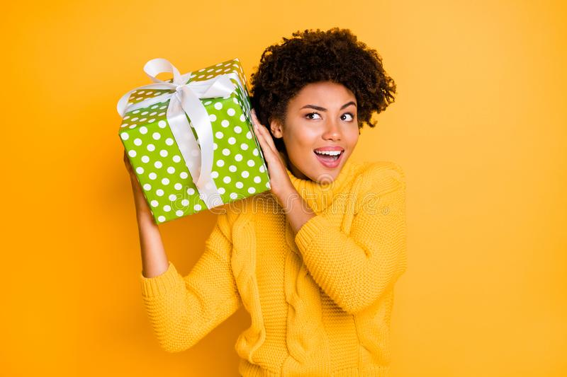 Photo of casual cheerful curly trendy confused girlfriend listening to wrapped box inner part wearing yellow sweater stock photography