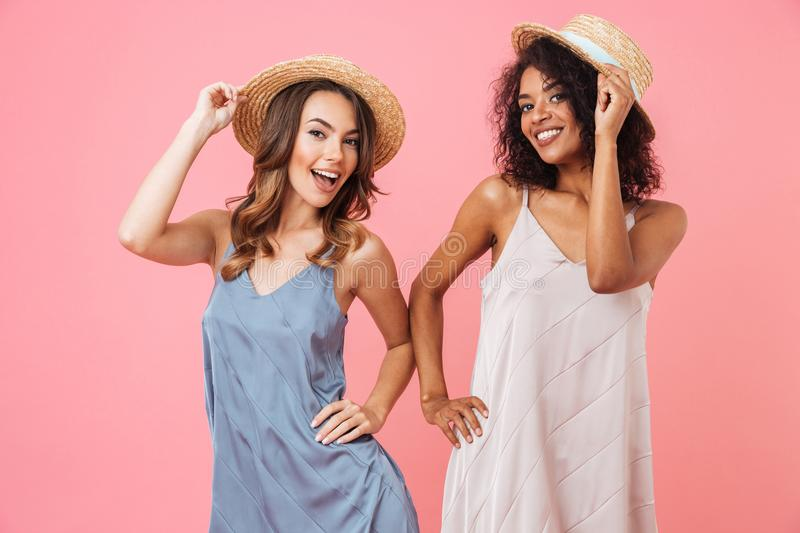 Photo of caucasian and african american women 20s wearing dresses smiling while posing at camera in stylish straw hats, isolated. Photo of caucasian and african stock photos