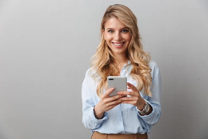 Photo of caucasian blond businesswoman with long curly hair smiling and holding smartphone royalty free stock photo