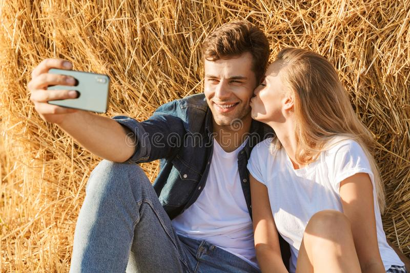 Photo of caucasian couple man and woman taking selfie while sitting under big haystack in golden field, during sunny day. Photo of caucasian couple men and women stock photo