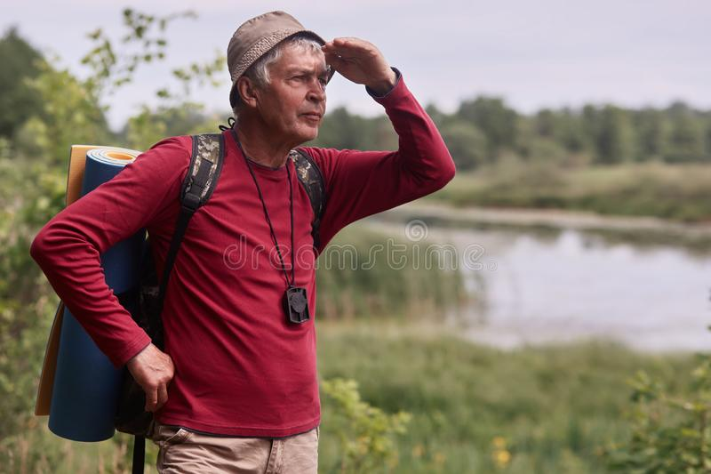 Photo of caucasian man hipster man with backpack and rug in nature background. Relax time on holiday, eldery male looking far away royalty free stock images