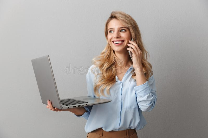 Photo of charming blonde woman 20s dressed in shirt smiling and talking on smartphone while holding silver laptop. Isolated over gray background royalty free stock image