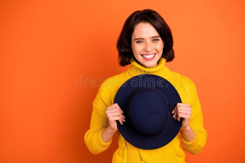 Photo of charming cheerful cute nice girl holding cap with her hands while isolated with orange background. Photo of charming cheerful, cute nice girl holding stock photo