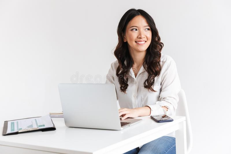 Photo of charming chinese businesswoman with long dark hair sitting at table and working with documents and laptop, isolated over stock photos