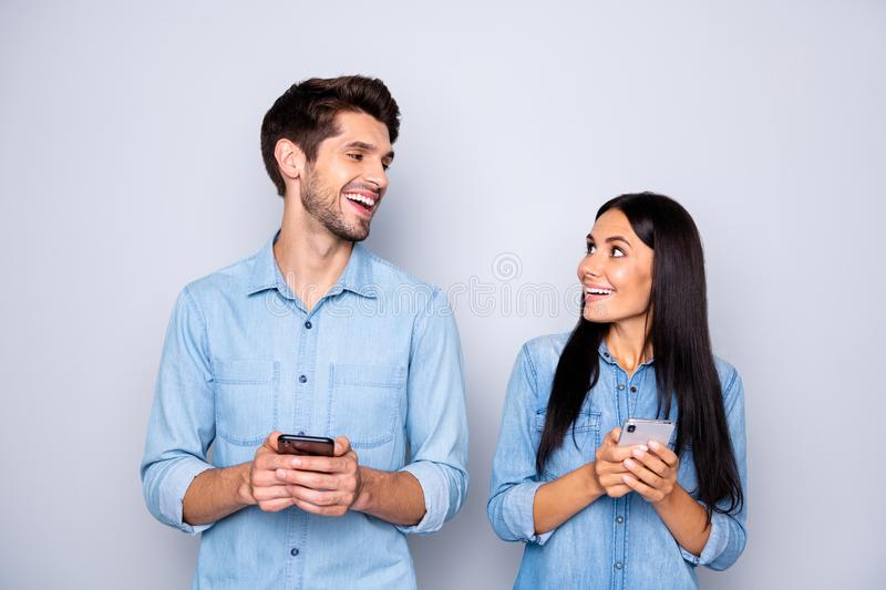 Photo of charming cute nice beautiful couple of two people spouses holding their phones reacting to something they have royalty free stock photo