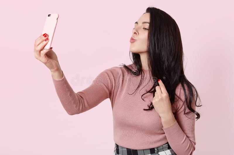 Photo of charming girl using smartphone for selfie. Attractive female with long dark hair makes selfie, keeps lips rounded, woman royalty free stock image
