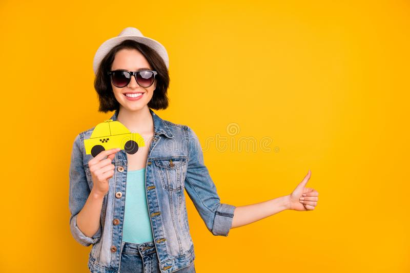 Photo of charming toothy beautiful interesting girl wearing cap jeans denim jacket adverting you some taxi while. Photo of charming toothy beautiful, interesting stock photos