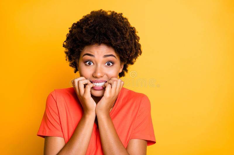 Photo of charming wavy attractive cute trembling girlfriend black skinned fearful biting her nails  with yellow royalty free stock photography