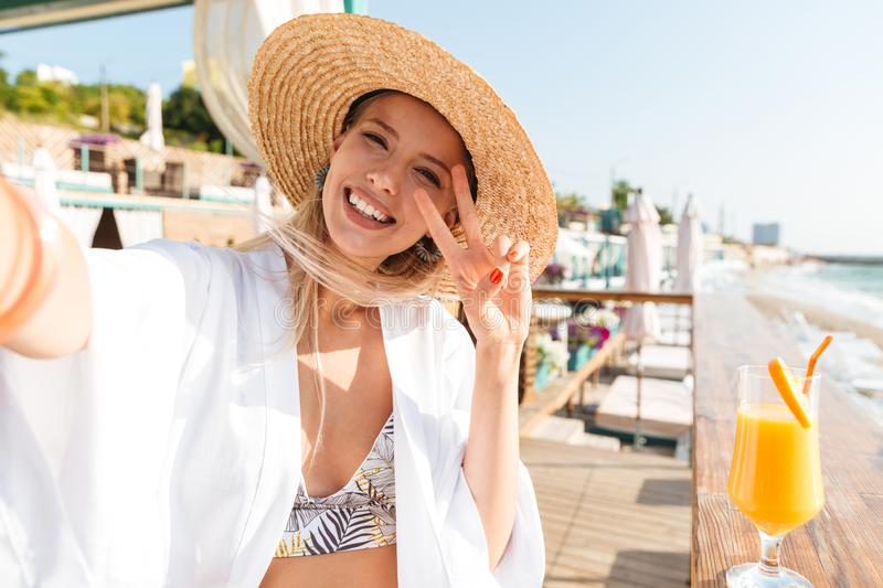 Photo of charming woman 20s in straw hat and swimwear taking selfie, while drinking orange juice in beach bar during vacation. Photo of charming woman 20s in stock photos