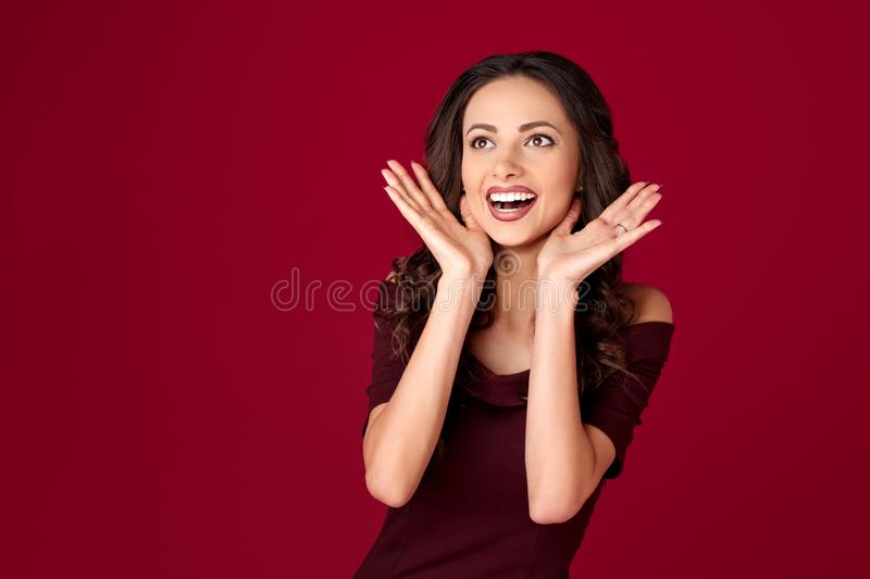Photo of charming young woman in maroon dress over red background. Photo of charming young woman in maroon dress over red background royalty free stock photo