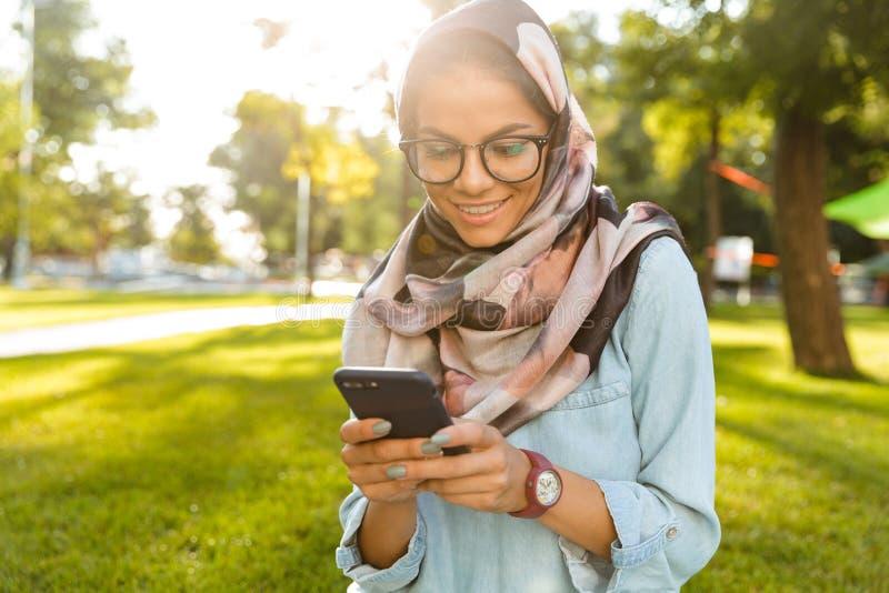 Photo of cheerful arabian woman wearing headscarf using mobile phone stock image