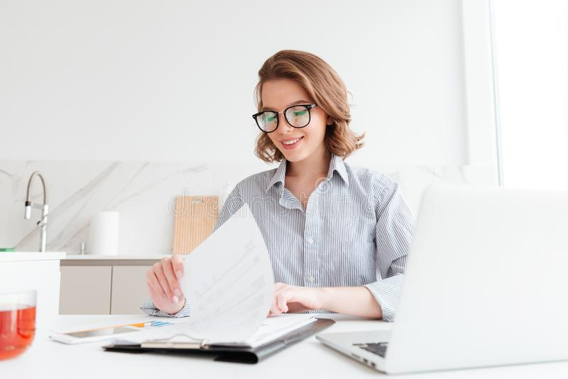 Photo of cheerful attractive woman in glasses reading new contra royalty free stock image