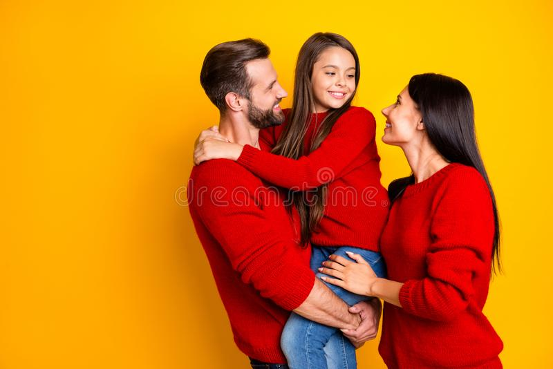 Photo of cheerful charming cute family with mommy and daddy embracing their daughter holding with hands wearing red stock photos