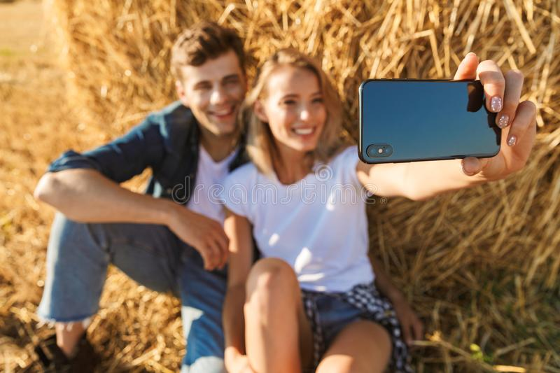 Photo of cheerful couple man and woman taking selfie on smartphone while sitting under big haystack in golden field, during sunny. Photo of cheerful couple men stock photo