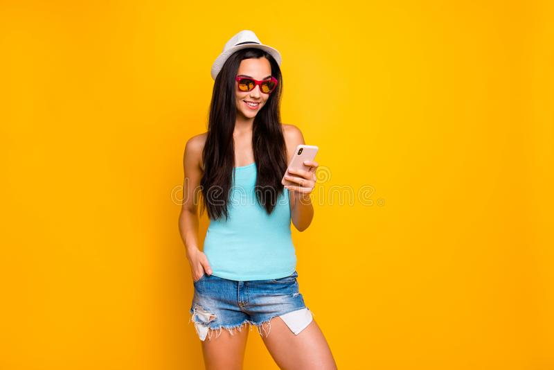 Photo of cheerful cute funky confident charming attractive youngster millennial looking into smartphone browsing wearing royalty free stock image