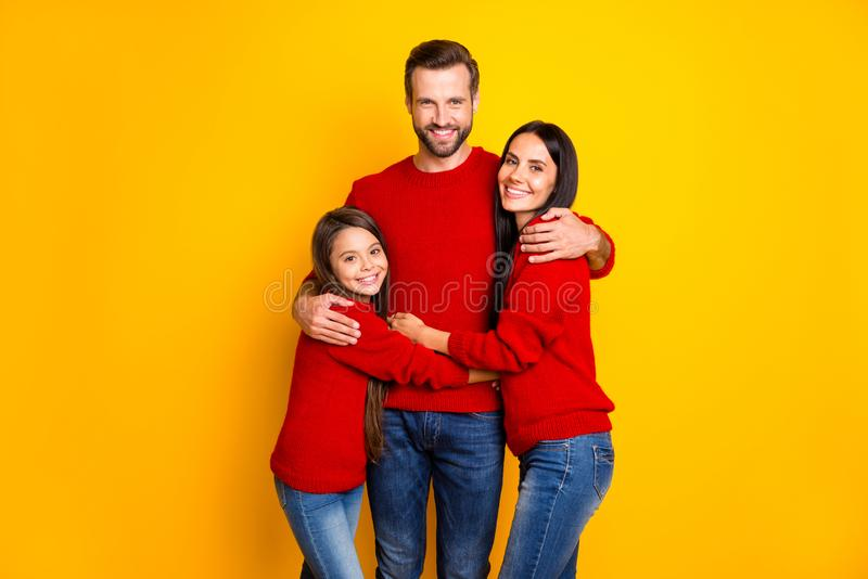 Photo of cheerful cute nice family wearing jeans denim red sweaters hugging embracing each other in love isolated over stock photo