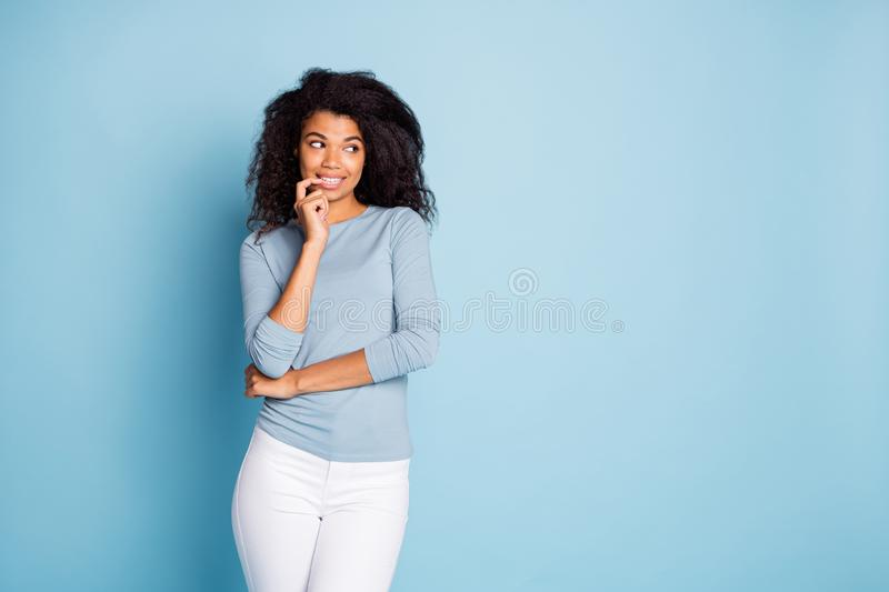 Photo of cheerful cute nice pretty girl biting nails looking into empty space planning her cunning idea in white pants. Photo of cheerful cute nice pretty girl royalty free stock photo