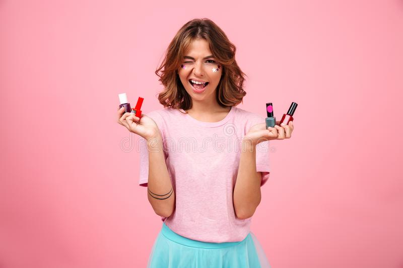 Cheerful emotional young woman holding nail polish stock images