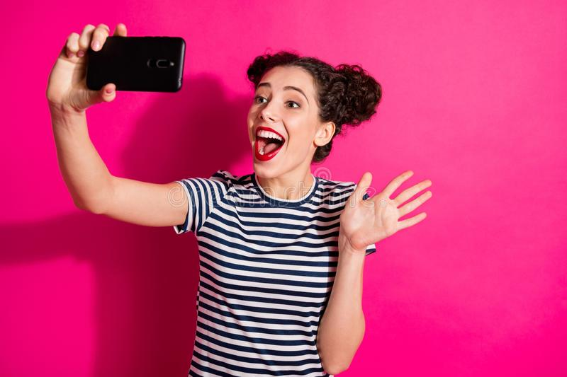 Photo of cheerful excited curly cute sweet nice girlfriend waving hand to ones she speak with by video call holding stock image