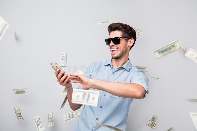 Photo of cheerful excited ecstatic overjoyed man throwing money away showing his wealthiness wearing denim isolated over royalty free stock image