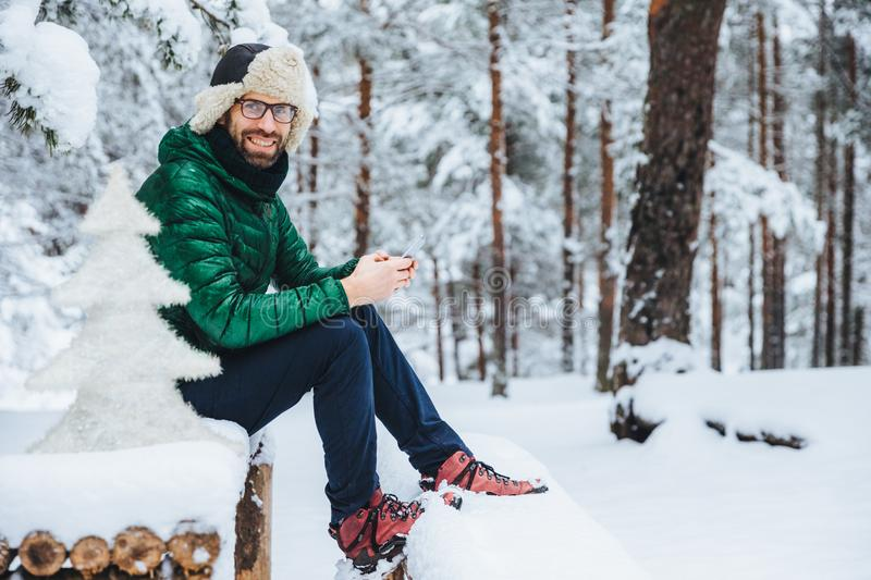 Photo of cheerful male types messages on smart phone looks directly into camera, sits in white winter forest, smiles happily, enjo. Ys communication, watches royalty free stock photo