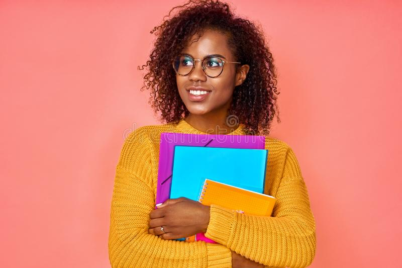 Photo of cheerful pleased African American student looks upwards, dreams about receiving a degree, carries papers and. Notepad, dressed in yellow jumper stock photos