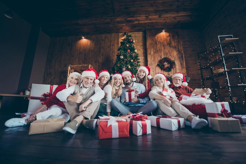 Photo of cheerful positive big family surrounded with gift boxed smiling toothily in front of christmas tree lights stock photos
